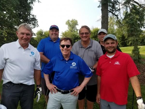Posing with former NFL player Doug Plank (white NPH USA shirt) and Bob Costas (blue NPH USA shirt) are Mark Stoudt, Art Zwemke, Mike Zwemke and Corey Tedford.